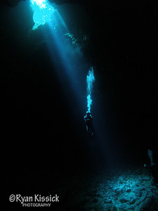Diver exhaling in magnificent underwater sunbeam