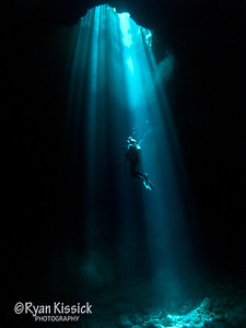 Diver looking up in beautiful underwater sunbeam