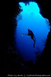 A photographer looks through the deep swim-through at Pohon Miring.  Banda Islands, Indonesia