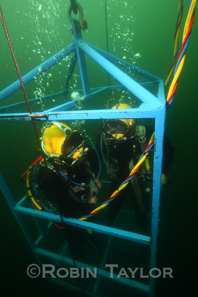 As the stage moves up through each decompression depth, the divers prepare to surface