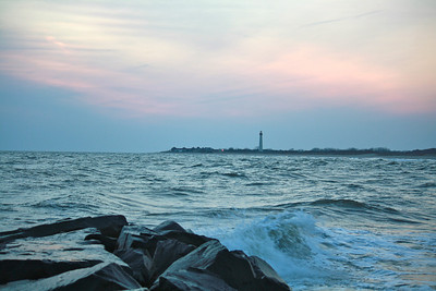 The Cape May Lighthouse, visible across the waves, stands in solitude against the light of early sunset.