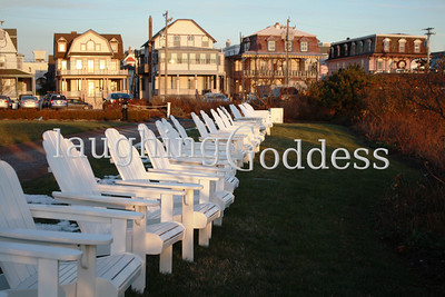 A chorus line of white wooden chairs faces the beach in Cape May, NJ. All that's missing from this idyllic image is a tall, cold glass of iced tea and a terrific beach book.