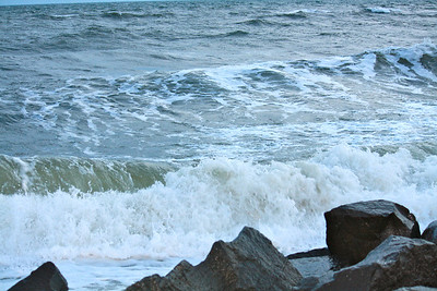 Rows of white cap waves form and crash on one of the prominent rock formations which graces the beach in Cape May, NJ.