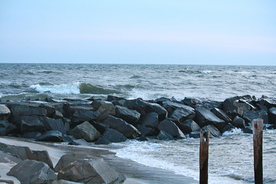 White cap waves rolling into a long rock formation on the beach in Cape May, NJ.