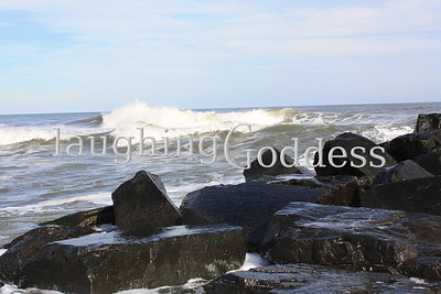 A white cap wave forms and looms in front of a rock formation in Ocean Grove, NJ. The close up image of the rocks offers an unprecedented view of tide pools forming between the massive stones.
