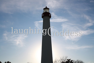 The Cape May Lighthouse stretches above the coast to stand against a nearly cloudless blue sky.