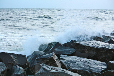 A close up photo of the black rocks which line the beach in Cape May, NJ. I was standing on the rocks just beyond the visible edge of this image when I snapped this photo. For my efforts, I was rewarded with a vicious soaking as this incoming wave broke.