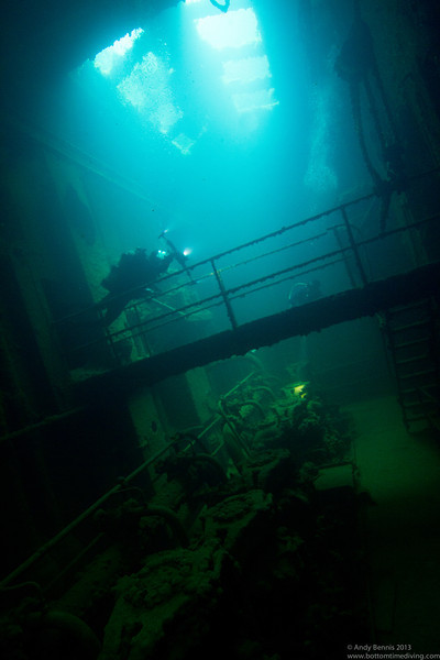 Divers exploring the engine room of the Kensho Maru.<br /> Truk Lagoon 2013