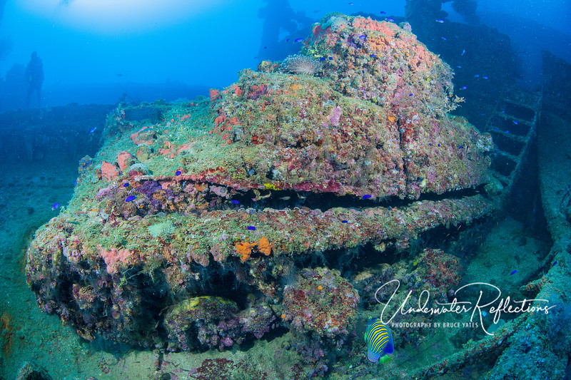 A colorful tank (minus the barrel) sits on the deck of a wreck.