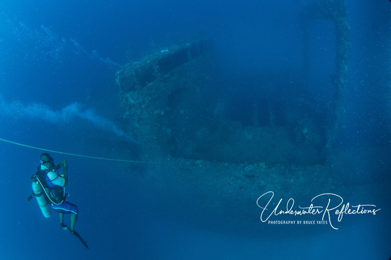 A dive guide watches as divers' bubbles emerge from the wreck below.