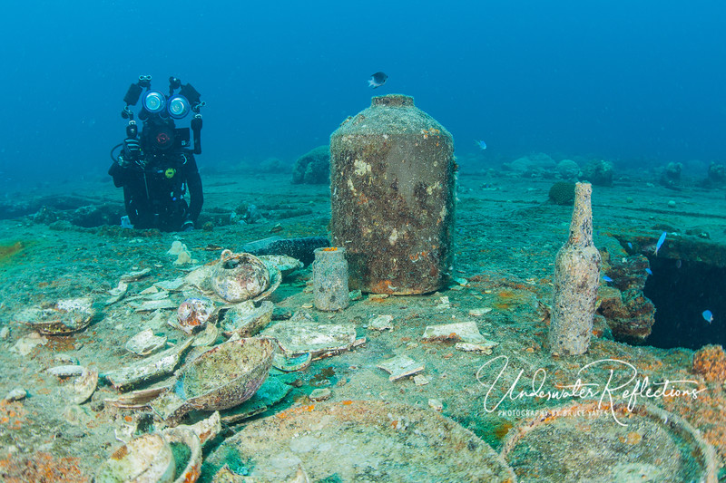 Assorted broken china, bottles, and other artifacts on the top (actually the upward side of a ship lying on its side), with another diver rising out of one of the windows from the interior of the wreck.