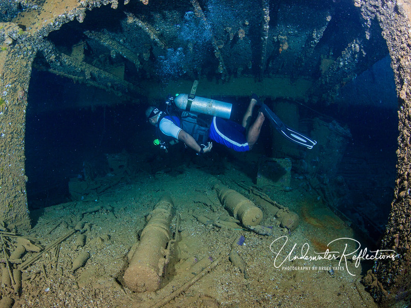 Chuukese dive guide swims through interior rooms with floors covered in debris - artillery shells and silt.