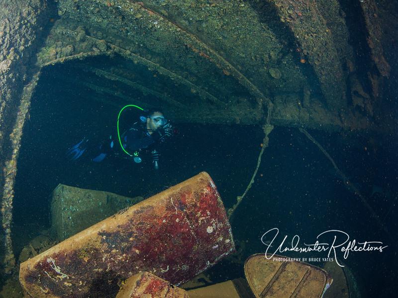 Diver swimming through pitch black interior rooms.