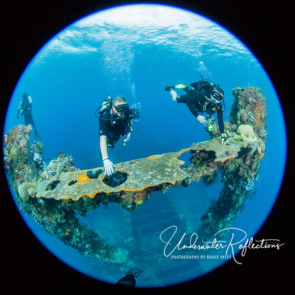 Divers hang onto a cross-beam decompressing at the end of a dive.