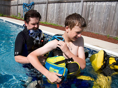"Zachary Salapatek, 14, of Sycamore (right) gets help from his uncle and buddy, John Noel, with putting on his scuba diving equipment during a class at Clifton Diving Center in Sycamore on Sunday, June 24, 2010.  Scuba divers are taught to never dive alone, and to rely on a ""buddy system"" to dive safely."