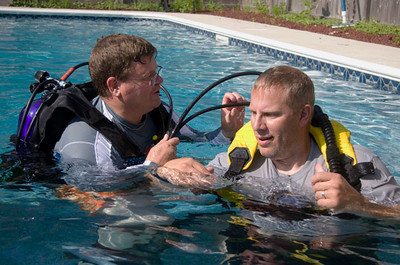 Kurt Clifton, owner of Clifton Diving Ventures in Sycamore (left) describes the various air hoses on a scuba tank to a student on Sunday, June 24, 2010.
