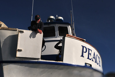 Crew member Kevin looks out from the open dive gate on the bow of the Peace.