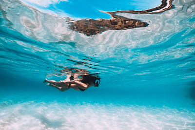 Young woman swimming underwater in the tropical blue ocean with white sand