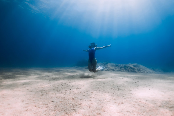 Lady freediver with fins posing and glides underwater in blue sea with sunlight.