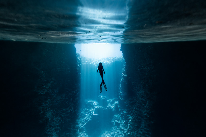 Charyse silhouetted as light pours into a sea cave on Vava'u, Tonga.