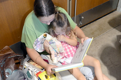 Jessica Weaver, 14, Selinsgrove, reads a book to her sister Violet, 2, while taking a break from the Union County library's book sale on Wednesday morning at the Faith Lutheran church in Lewisburg.