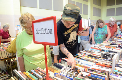 Wes Boudman, Bloomsburg, searches through the rows of books for sale at the Union County library's book sale at Faith Lutheran church in Lewisburg on Wednesday morning.