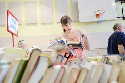 Laura DeSantis, Winfield, holds onto her books while checking out another one for sale at the Union County library book sale on Wednesday morning at the Faith Lutheran church in Lewisburg.