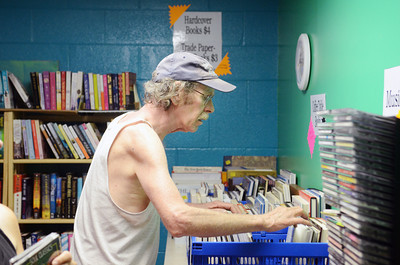Matt Langman of Woodward searches through piles of books for sale on Wednesday morning at the Union County library book sale at the Faith Lutheran church in Lewisburg.