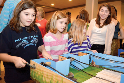 Members of Girl Scout Troop 1105 from Beaver Springs, Kayla Swope, 11, Chloe Freed, 9, and Chloey Yerger, 9, race using gears as Taylor Shumann explains the project to them during the Gizmo Expo on Monday at Bucknell.