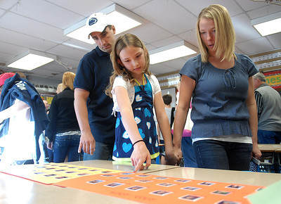 Emily Katz, 9, looks through photos of former third grade students with her parents, Ron and Jamie, during the open house Tuesday May 10, 2012 at Buffalo Crossroads Elementary School.