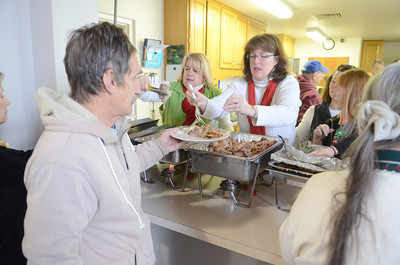 Frank Musser, left, of Milton, gets a serving of turkey and other tasty items from Marguerite Santorine and Beth Shutt who were volunteering their time to help serve a free community Christmas dinner at the First Presbyterian Church in Lewisburg on Wednesday.