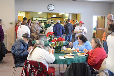 People sit down to enjoy their Christmas dinner as others line up to get theirs at the free community Christmas dinner on Wednesday at the First Presbyterian Church in Lewisburg.