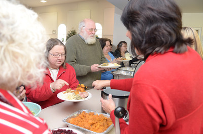 Yvonne and Dave Coup of Milton go through the line at the First Presbyterian Church in Lewisburg on Wednesday during their free community Christmas dinner.