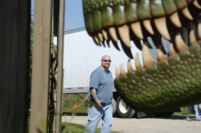 Truck driver Chuck Kumalaa, Ohio, checks out the load he was carrying to Clyde Peeling's Reptiland on Friday which included several life size and animated dinosaurs.