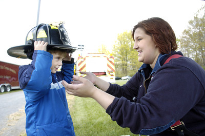 Max Ferry, 4, left, Milton, tries on a fire fighter's helmet with the help of volunteer Jordin Langin of the Muncy Area Volunteer Fire Company on Wednesday at the Emergency Preparedness Day at the FCC Allenwood Training Center.