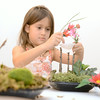 Veronica Young, 6, puts a seashell on her fairy garden as she and others created a home for faries on Tuesday at the Packwood House in Lewisburg.