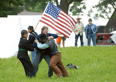 Chase Hornberger, 15, of Higgins, Pa. struggles to return to his troops as Nathaniel Weaver, left, and Mitchell Jodon, both of Lewistown stuggle to bring him to the hospital tent during a Civil War reenactment in Hartleton Saturday June 2, 2012.