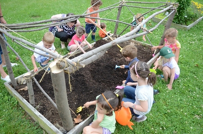 Kids help plant a garden at the Union County Library on Monday as part of the Kids In The Garden program.