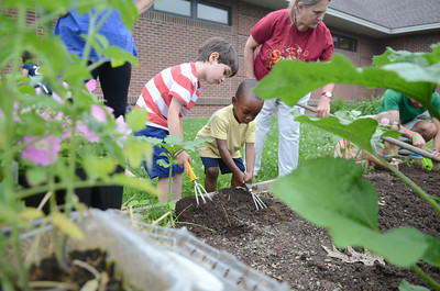 Patrick Mulhern, 5, left, Lewisburg, and Theodore Broe, 2, Lewisburg, work together to loosen up soil before planting a garden at the Union County Library on Monday as part of the Kids In The Garden program.
