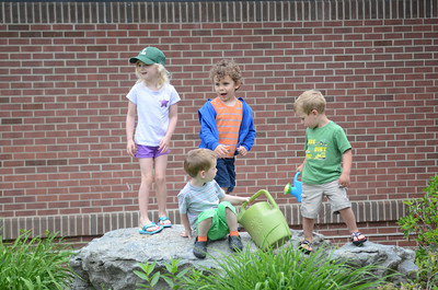 Shea Lane, 5, left, Lewisburg, plays with Cache McBride, 3, Lewisburg, Caleb Orsborn, 3, Lewisburg, and Tate McIlwaine, 3, Lewisburg, on a rock at the Union County Libary while they waited for the Kids In The Garden program to begin on Monday.