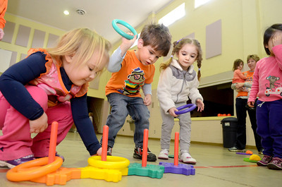 Rae Lynn Wise, left, Max Lynch, and Penelope Polimenakos, play ring toss on Friday at the Kids of the Kingdom Preschool during their sports day.