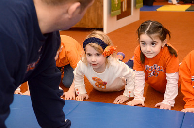 Bucknell men's wrestling coach Dan Wirnsberger does pushups with Nora Lynch and Angelina Seeba at the Kids of the Kingdom Preschool on Friday during their sports day.