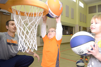Bucknell head women's basketball coach Aaron Roussell, left, watches Austin Weikel take a shot during a sports day at the Kids of the Kingdom Preschool on Friday.