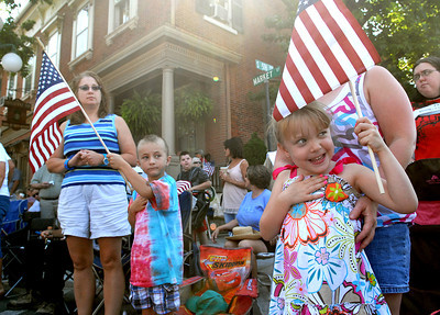 James Donlin, 5, left of Mifflinburg, and Mindy Roat, 5, of New Berlin stand and honor the flag as the color gaurd leads the way Saturday June 30, 2012 at the Lewisburg 4th of July Parade.