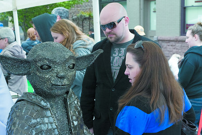 Derek and Alicia Knouse of Lewisburg survey the works of metal artist Roland S. Paronish during the Lewisburg Arts Festival on Saturday