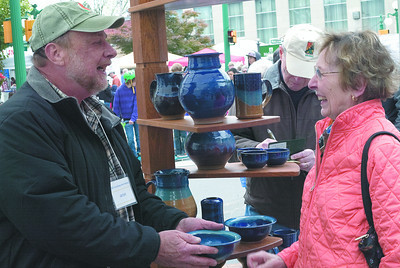 Bill Lynch of Penns Creek Pottery shows a bowl to Martha Lynch of Coal Township on Saturday at the Lewisburg Arts Festival