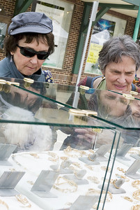 Bea Heid, right, of Lewisburg, and Avis Hans, of Milton, check out jewelry at Brian Mariano's stand during the Lewisburg Arts Festival on Saturday.