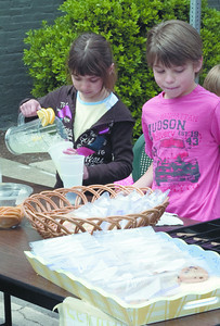 Madison Dominick, 8,  and Ethan Dominick, 8, both of Lewisburg, work at a lemonade stand during the Lewisburg Arts Festival on Saturday. The stand was raising money to help save manatees.