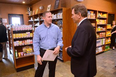 Lewisburg Pharmacy owner Brad Gill, left, talks with DCED Secretary Dennis Davin at the pharmacy on Thursday morning.