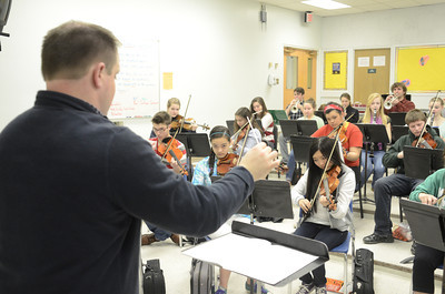 Lewisburg High School instrumental music teacher Justin Hill, left, conducts a practice on Wednesday during class.